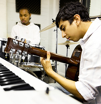 Young musicians play the guitar and drums together